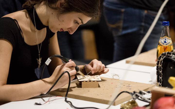 A woman is soldering a wire.