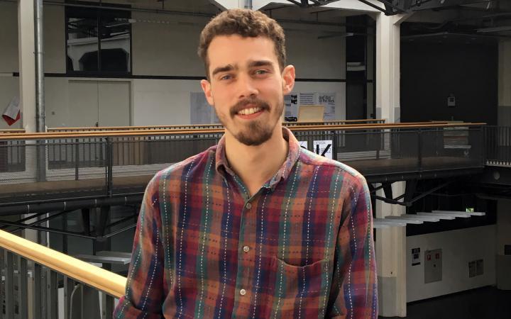 Portrait von George Barker: Ein junger Mann steht im ersten Stock des Lichthofs der HfG Karlsruhe