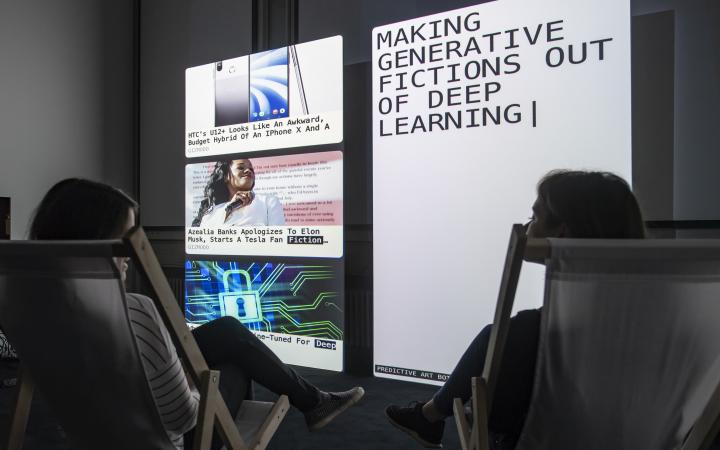 """Two people sit in deck chairs in front of two large screens. On the right screen is written """"Making generative fictions out of deep learning""""."""