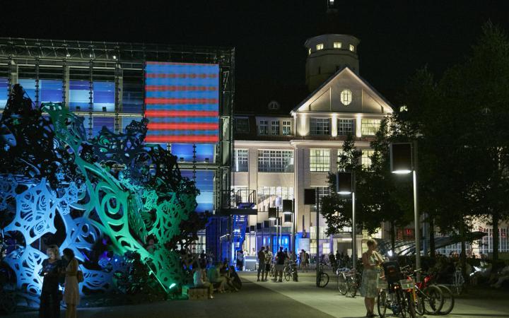 Hallengebäude mit einer  beleuchteten Skulptur bei Nacht