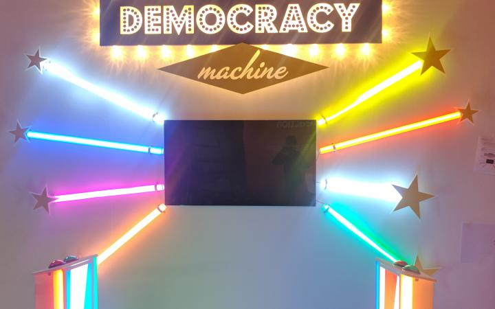 Front view of The Democracy Machine! In the middle of a wall is a television set installed around it, three colorful color tubes are arranged like sunbeams. In front of it are two podiums with buttons.
