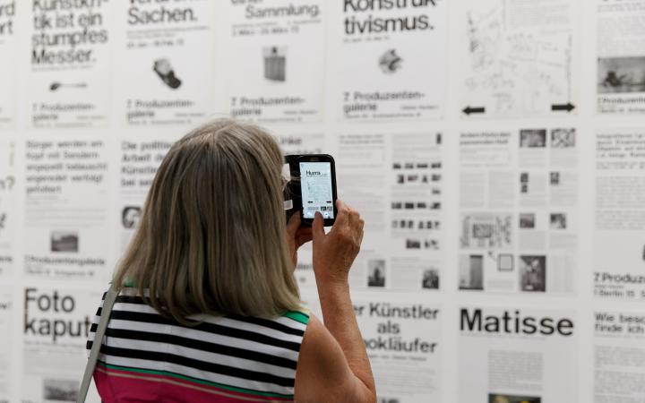 A visitor takes a picture of a wall full of typography posters with her smartphone.