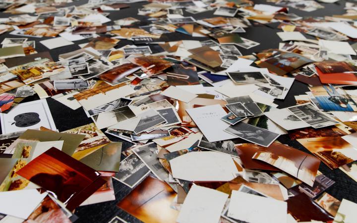 Eine Installation von Dieter Hacker. Auf dem Boden des Ausstellungsraums sind farbige Fotografien verteilt.