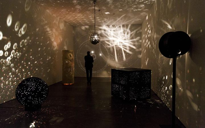 A person standing in an exhibition space with wall projections