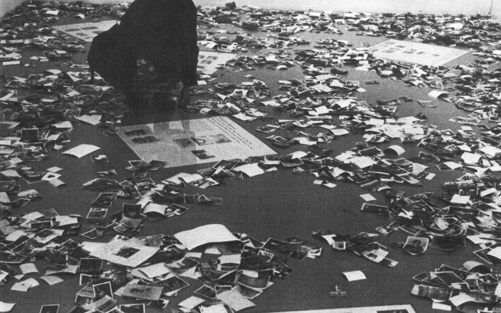 Die Schwarzweiß-Fotografie zeigt viele auf dem Boden zerstreute Fotos.
