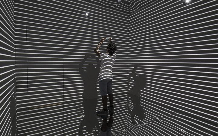 Man in a room which is striated by light.
