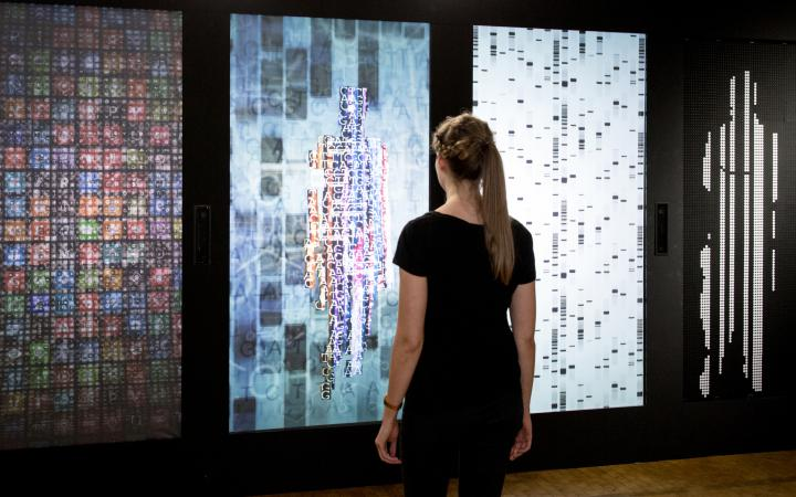 Eine Frau steht vor der Installation YOU:R:CODE, einer Mehrkanalprojektion, die sie in Datenform darstellt