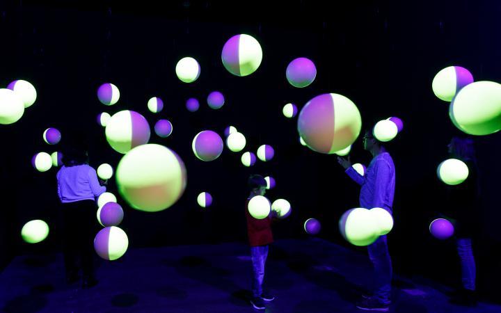 In einem dunklen Raum hängen halbseitig-fluoreszierende Styroporkugeln von der Decke mit denen drei Besucher interagieren