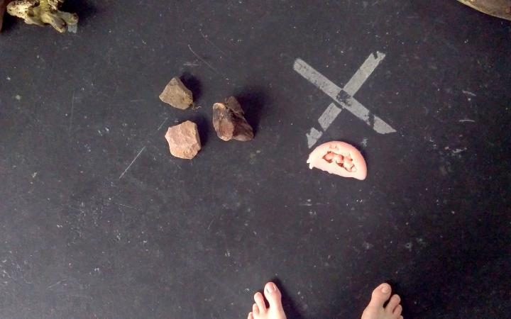 Two pieces of wood, three stones and a pair of feet can be seen on a black background.