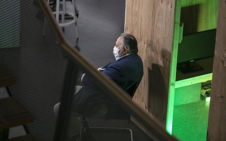 Peter Weibel sits on a chair with a mouth-and-nose mask and looks out of the picture.