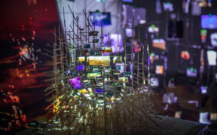 Zu sehen ist eine filigrane Installation aus dünnen Stäben, an denen kleine Papierstückchen befestigt sind. Auf jedem Stückchen Papier ist eine Lichtprojektion zu sehen.