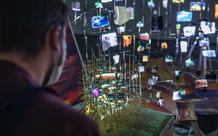 Das Foto zeigt eine Nahaufnahme der künstlerischen Arbeit von Sarah Sze mit dem Namen »Flash Point«. Es ist eine unglaublich detaillierte Bildflut, die auf einem fragilen Nest-ähnlichen Gerüst aufgebaut ist.