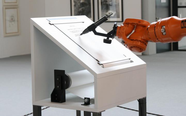 Das Bild zeigt einen Roboterarm, der ein Manifest verfasst