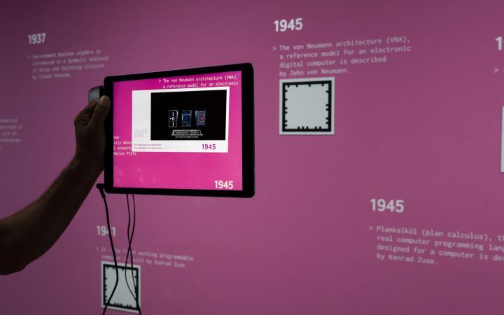 Eine Hand hält ein Tablet vor eine pinkfarbene Wand.