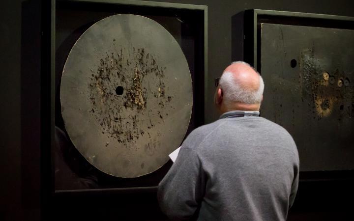 Das Foto zeigt den Rücken eines glatzköpfigen Mannes vor einem Werk von Aldo Tambellini.