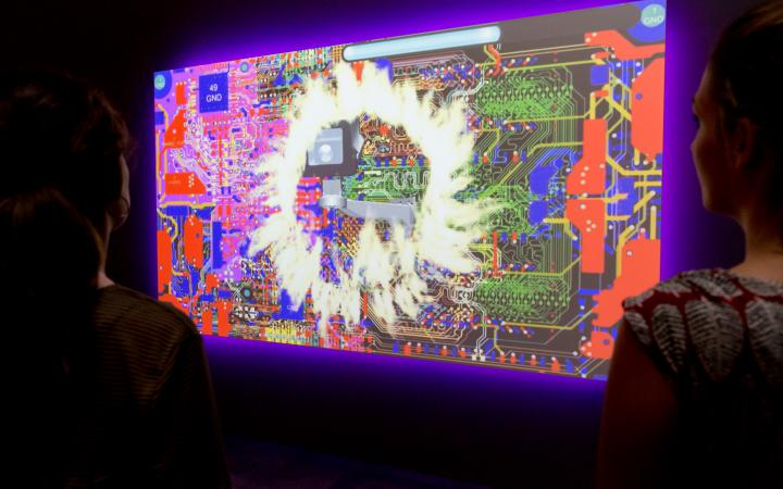 Two visitors are looking at a video artwork which shows mashup of a computers hardware parts and flames