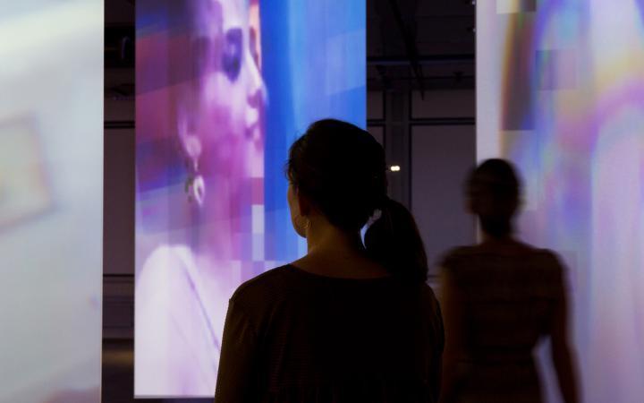 Die Silhouetten zweier Besucherinnen vor bespielten Leinwänden