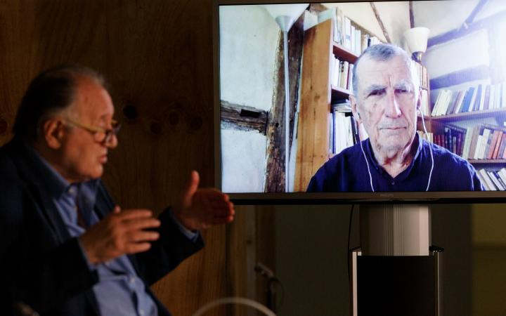 Peter Weibel sits in front of a large screen on which Bruno Latour can be seen.