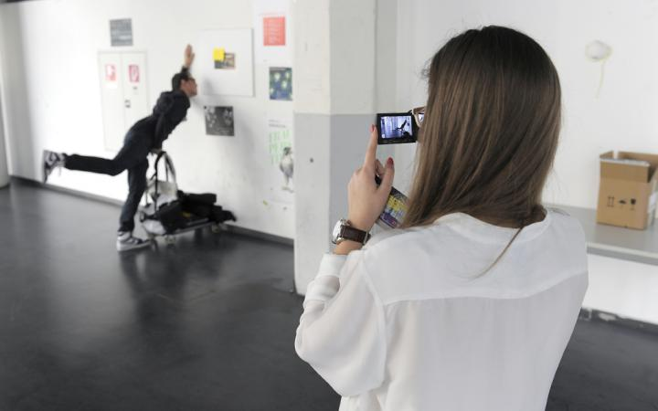 A young woman is fotografing a man. He is posing for the picture and is feigning to crash into the wall while pushing a dolly.