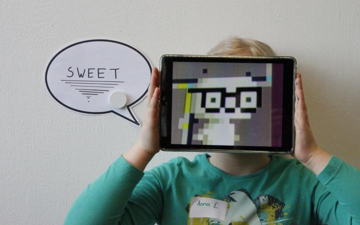 """Performance, bei der ein Mädchen ein iPad vor ihr Gesicht hält, auf dem eine Figur aus Pixeln angezeigt wird. Neben ihr ist in einer Sprechblase das Wort """"Sweet"""" zu lesen."""