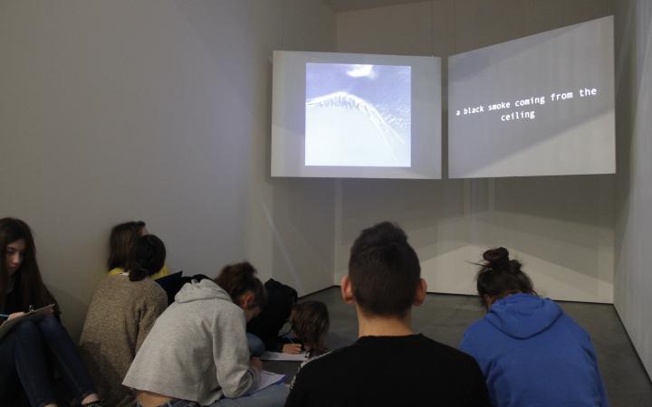 Jugendliche sitzen vor zwei großen Projektionsflächen, auf denen ein Bild und die Zeile »a black smoke coming from the ceiling« zu sehen sind.