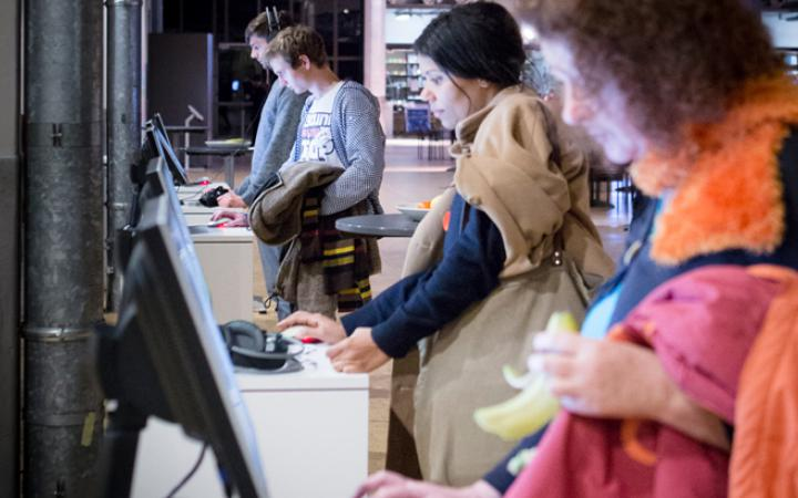 Several People standing in front of computer stations