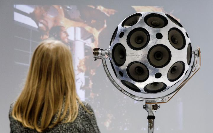 A woman stands in front of a silver sphere of loudspeakers