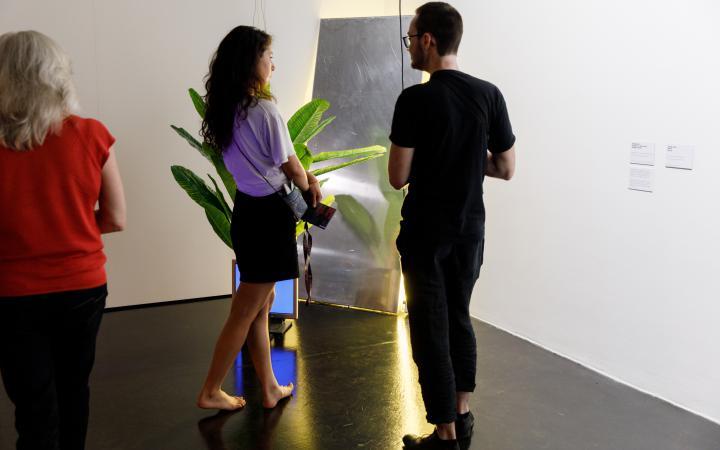 Das Foto zeigt eine barfüßige Besucherin und einen schwarz gekleideten Besucher vor einer an der Wand angelehnten Installation neben der eine Pflanze steht