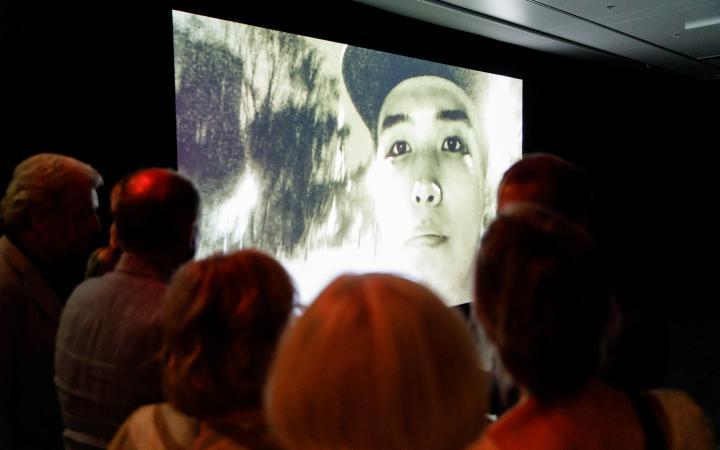 Das Bild zeigt eine Menschenmenge vor einem riesigen Bildschirm auf dem gerade ein asiatischer junger Mann mit Cappy zu sehen ist.