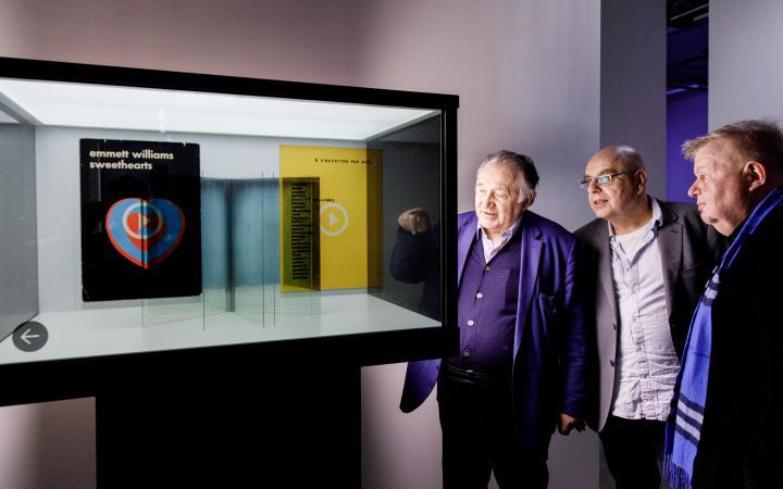 Peter Weibel vor einer Vitrine mit virtuellen Büchern in der Ausstellung »Writing the History of the Future«