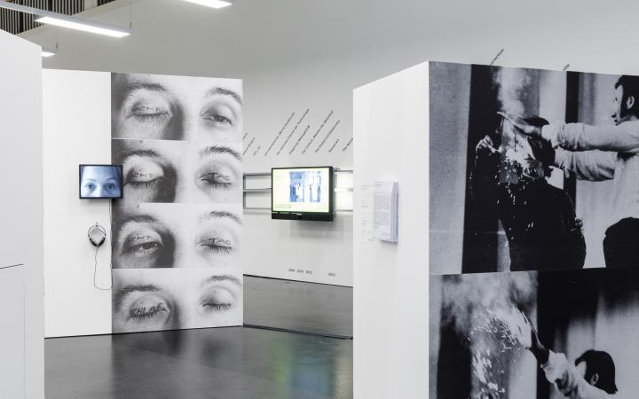 In der Mitte zwei Stellwände, auf der rechten Wand ein Bildschirm und Schrift. Auf der einen Stellwand, links hinten, ein kleiner Bildschirm mit Kopfhörer und aufgedruckte große Fotos von Augen, auf deren Lidern »Tag«, »Nacht« oder »Schlaf« stehen.
