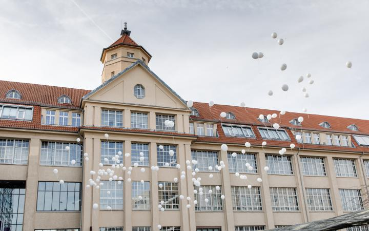 White balloons floating in front of the ZKM building.