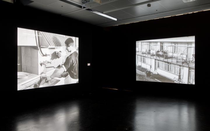 Das Foto zeigt den Ausstellungsraum mit zwei großen Leinwänden links und rechts an den Wänden. Auf der linken Leinwand ist eine Frau beim Abwasch zu sehen, auf der rechten Leinwand ein Seniorenwohnheim von außen und Personen, die auf Balkonen sitzen.