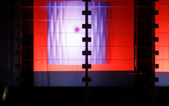 Zu sehen ist der ZKM Subkubus mit einer Projektionsfläche, auf denen Farben oszillieren.