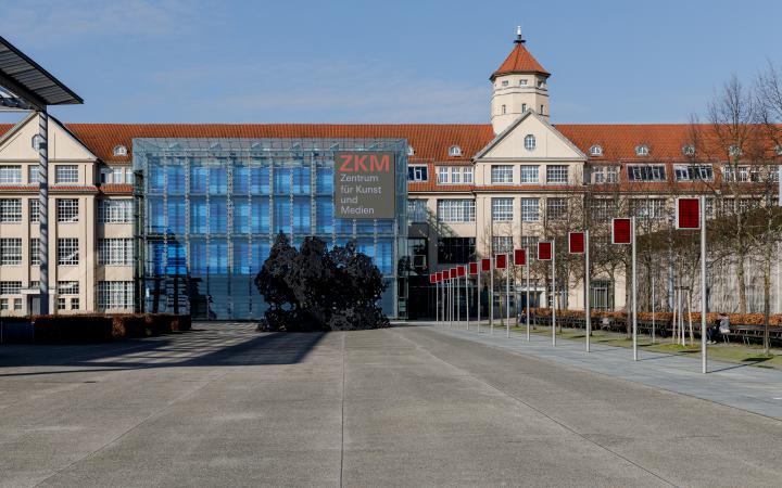 Das ZKM von außen. Man sieht frontal den Kubus mit der totalen Verglasung und den davorstehenden Klangpavillon, das lange Industriegebäude des ZKM sowie den Platz der Menschenrechte mit den mehreren elektronischen Flaggen, die in einer Reihe stehen