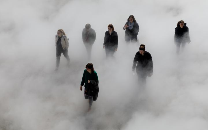 The photo shows seven laughing people walking across the Human Rights Square, partly covered by fog.