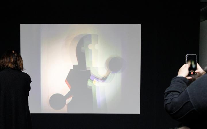 Das Foto zeigt eine große weiße Leinwand auf der eine Bauhaus Figur zu sehen ist.