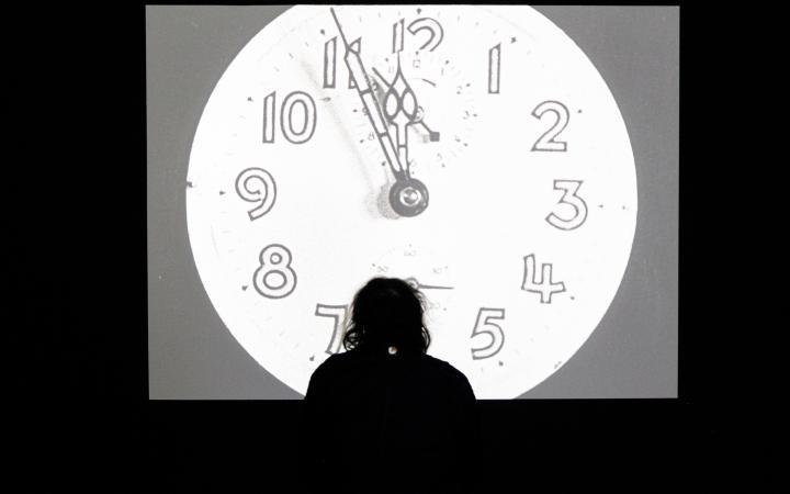 Das Foto zeigt die Silhouette einer Person, die sich auf einer großen Leinwand einen schwarz/weiß Film anschaut. Auf der Leinwand schlägt eine analoge Uhr gleich Zwölf. Das Licht der Leinwand fällt einen rundes verschwommenes Licht auf dem Boden.