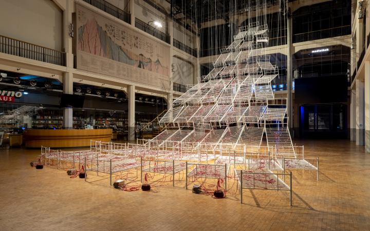Installation view of Chiharu Shiota's »Connected to Life«. On view are several hospital bed frames hanging from the ceiling. Red liquid flows through transparent tubes on the beds.