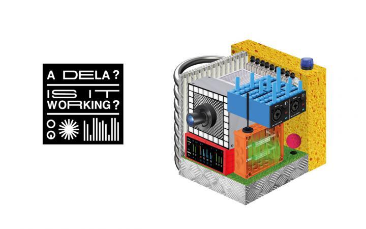 Zu sehen ist ein schwarzes Viereck, in welchem der Schriftzug A Dela? und Is it working? steht. Rechts daneben ist ein Würfel aus verschiedenen Komponenten, wie zum Beispiel einem Schwamm und eine Art Legostein zu sehen.