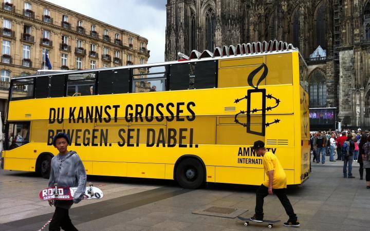 Gelber Doppeldeckerbus von Amnesty International