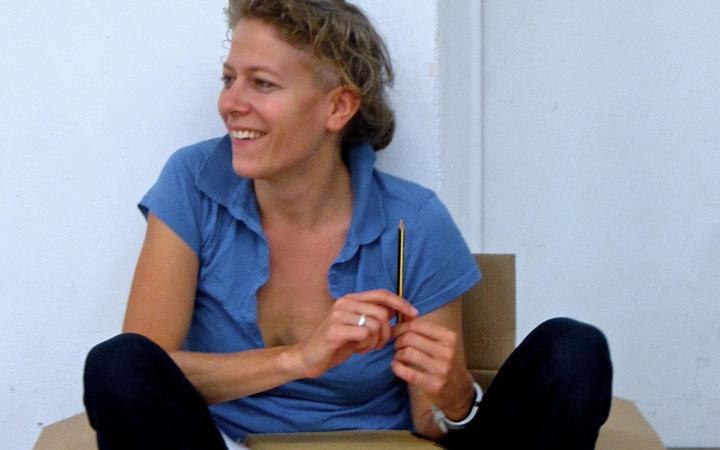 Anja Konjetzky sitzt lässig in einem Pappkarton und hält einen Bleistift in der Hand.