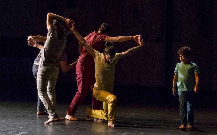Vier einfarbig bunt gekleidete Tänzer in verschlungener Tanzposition und ein in grün gekleideter Junge.