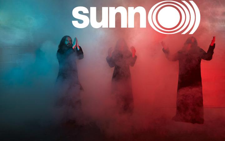 Die drei Musiker der Metalband »Sunn O)))« stehen im blau, weiß und roten Nebel.