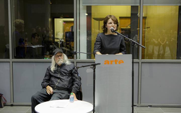 Links im Bild sitzt Ira Schneider, Medienkünstler, auf einem Stuhl und hört Daria Mille, Kuratorin am ZKM, bei ihrem Vortrag zu.