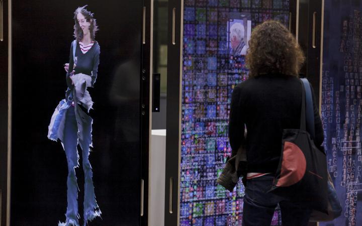 Eine braunhaarige Frau steht vor der Kunstinstallation YOU:RE CODE und sieht ihre digitale Spiegelung.