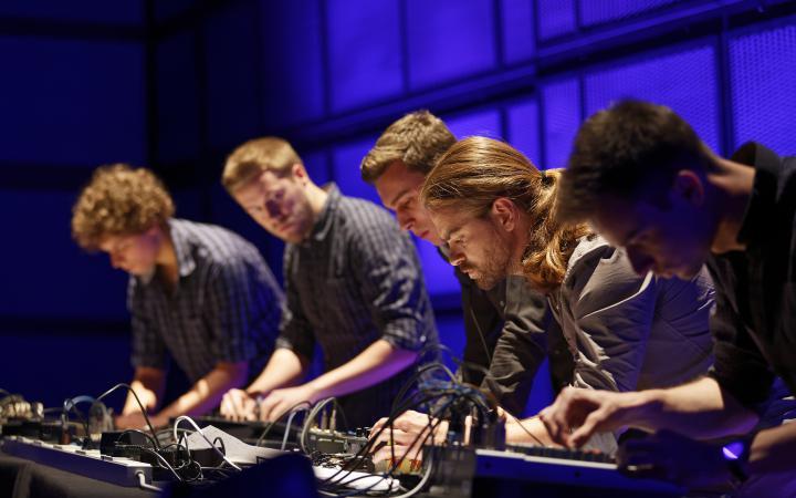 Fünf junge Männer stehen konzentriert vor einem Mischpult