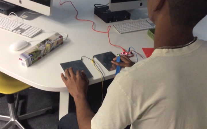 Ein Junge sitzt vor einem Rechner, auf dem Tisch vor ihm liegen zwei Platten, ein selbstgeebauter Controller zum Steuern seines Videospiels, auf denen er seine Hände liegen hat.