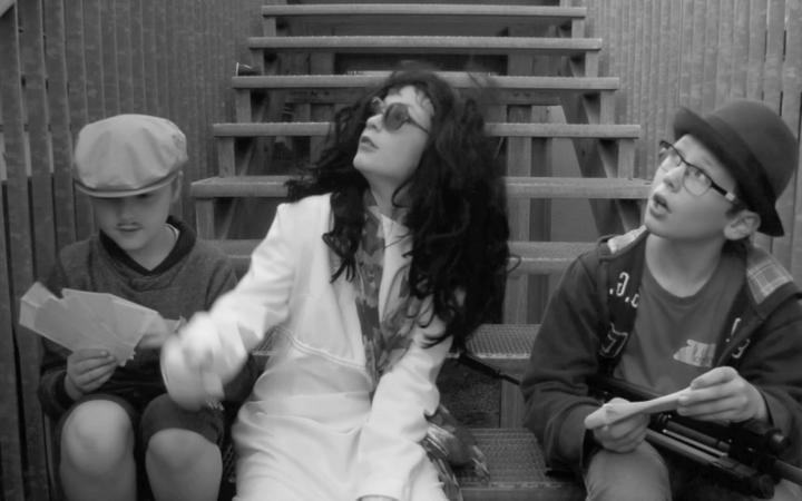 Drei Kinder sitzen in theatralischer Verkleidung auf einer Treppe. Zwei schauen überrascht nach oben, eines auf Spielgeld in seinen Händen.