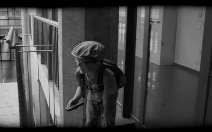 Ein Junge hält eine Fernbedienung in der Hand und lacht aus vollem Hals.